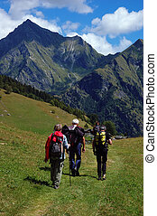 Trekkers walking along a mountain path, west Alps, Italy.