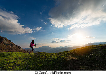 Trekking at sunset in the mountains alone
