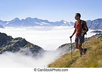 Trekking in the Alps - Man trekking in the Alps over the...
