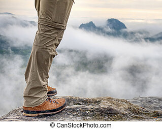 Trekking shoe and legs on rock. Outdoors achievement -...