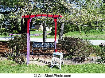 Trellis being Painted Red in Garden