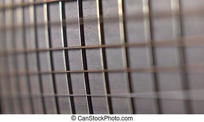 Trembling guitar strings against fret. Music performance. 4K...