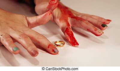 Trembling young woman hands with bloody fingers over ring