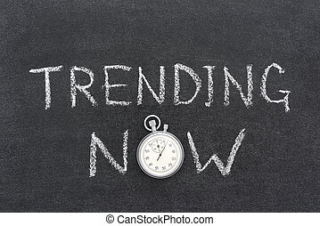 trending now phrase handwritten on chalkboard with vintage precise stopwatch used instead of O