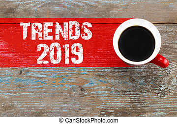 Trends 2019 / Cup of coffee with trends inscription on wooden background