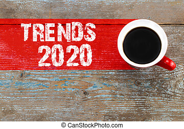 Trends 2020 / Cup of coffee with trends inscription on wooden background