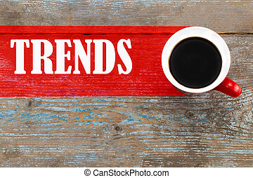 Trends / Cup of coffee with trends inscription on wooden background.