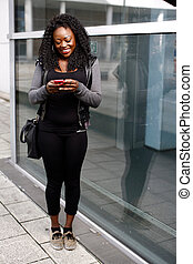 Trendy African woman reading a text message