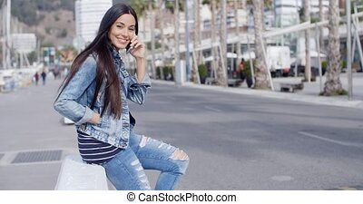 Trendy attractive young woman in a denim outfit perching on...