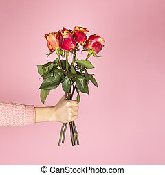 Beautiful bouquet of pink roses in a female hand on pink background.