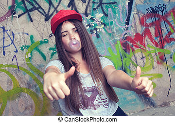 trendy beautiful long haired model posing on graffiti...