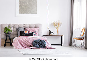 Trendy bedroom with orange chair