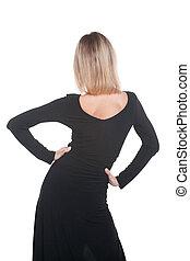 Trendy blonde woman in black dress standing back