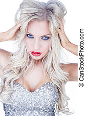 Beautiful alluring trendy blue-eyed blond woman with long blond hair and red lipstick in an off the shoulder silver dress