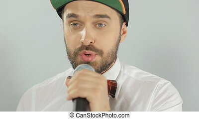 Trendy blue-eyed man with a mustache and beard sings into a microphone