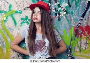 trendy, bonito, haired longo, modelo, posar, perto, pintado, wall., vermelho, cap., cinzento, t-shirt.