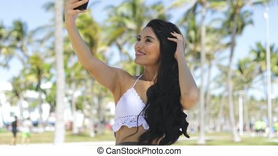 Trendy brunette taking selfie in sunshine - Content ethnic...
