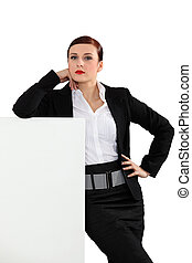 Trendy businesswoman with a board left blank for your message
