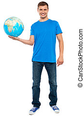 Trendy casual guy posing with a globe