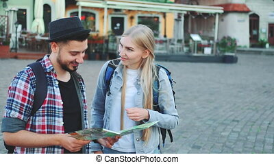 Trendy couple of tourists finding necessary destination on map and admiring surroundings. They standing on city square.