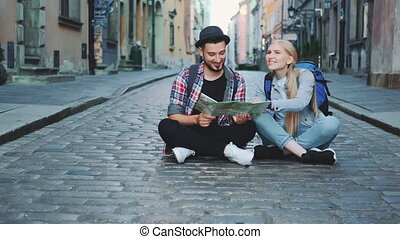 Trendy couple of tourists using map, sitting on pavement and admiring historical surroundings. They are excited and smiled.