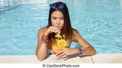 Trendy elegant young woman sipping a cocktail