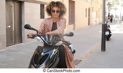 Trendy ethnic woman sitting on scooter on street - Stylish ...