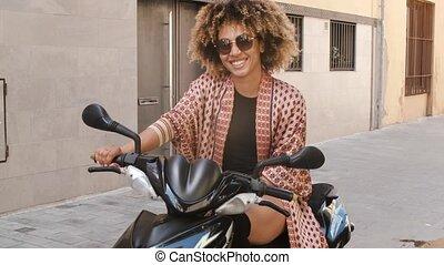 Trendy ethnic woman sitting on scooter on street - Stylish...