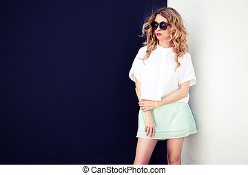 Trendy Fashion Hipster Girl at Contrasted Wall