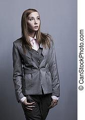 Trendy fashion model posing in grey costume. Studio shot