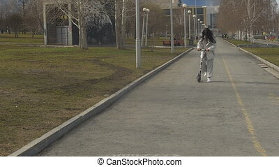 Trendy female riding scooter