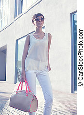 Trendy girl in sunglasses.beige blouse. white shirt. beige leather bag. high heels