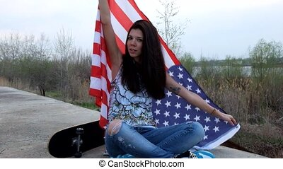 trendy girl posing with american flag and skateboard sitting  crossed legs outdoors.