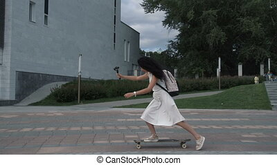 Trendy girl taking selfie while riding longboard