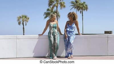Trendy girls chilling on seafront - Laughing multiethnic...