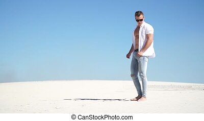 Trendy guy in jeans, wearing glasses and a white shirt standing barefoot on the sand in the desert