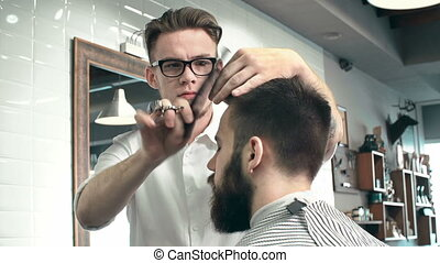Trendy Haircut - Front view of male hairstylist focused on...