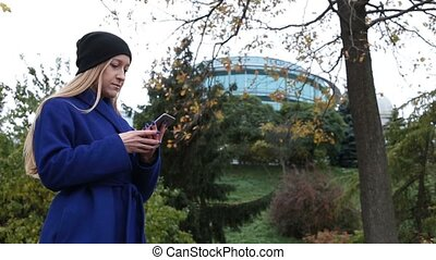 Trendy hipster girl texting on phone in autumn - Portrait of...