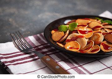 Trendy homemade breakfast, pancake cereal, mini pancakes on dark plate on grunge gray concrete background