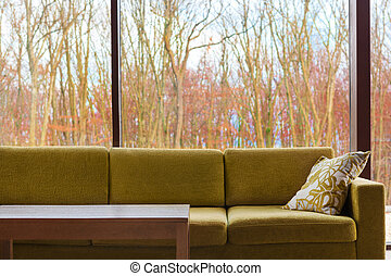 Trendy interior design. - Green modern couch against glass ...