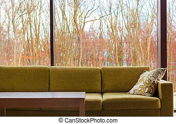 Trendy interior design. - Green modern couch against glass ...