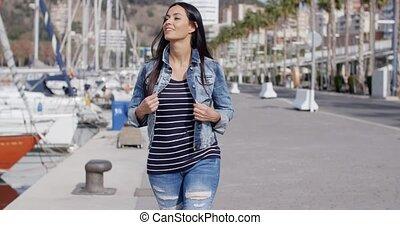 Trendy jaunty young woman enjoying a stroll along a...