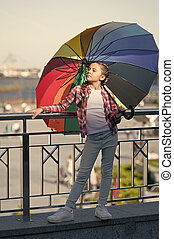 Trendy kid. Colorful accessory. Girl adorable child long hair walking with umbrella. Positive and optimistic concept. Colorful accessory positive influence. Bright umbrella. Under big umbrella