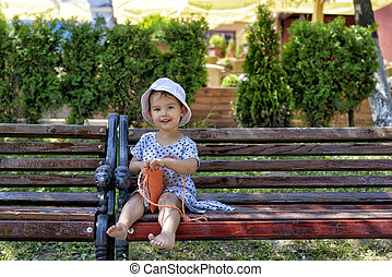 trendy little girl sitting on a wood bench with her handbag