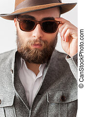 Trendy look. Close up portrait of handsome young man in casual wear adjusting his sunglasses