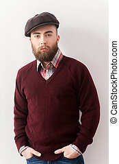 Trendy look. Handsome young man in hat leaning at the wall and looking at camera