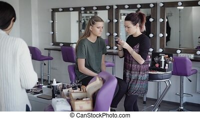 Trendy makeup artist builds artificial eyelashes to popular theater actress before the performance. Assistant at the forefront in the beauty salon is preparing a place for another client.