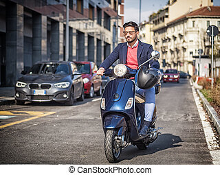 Trendy man on scooter in city