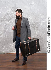 trendy man with travel suitcase. Vintage trip bagage. Modern life. Male fashion model. Mature businessman with beard. Travelling fot business. Casual style. Brutal bearded hipster in denim wear