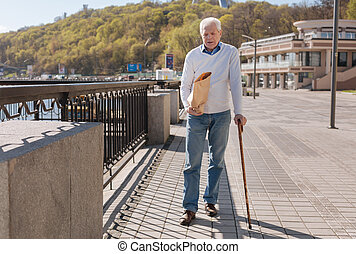 Trendy pensioner going home with beverage in the park